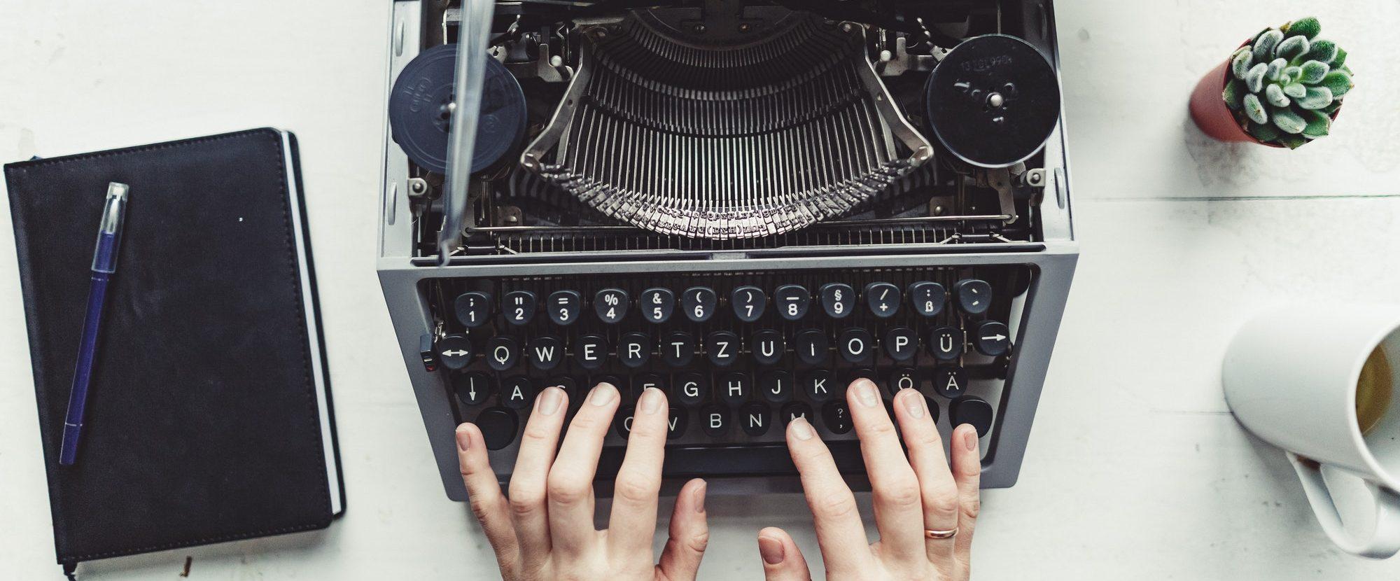 Writer typing with retro writing machine.